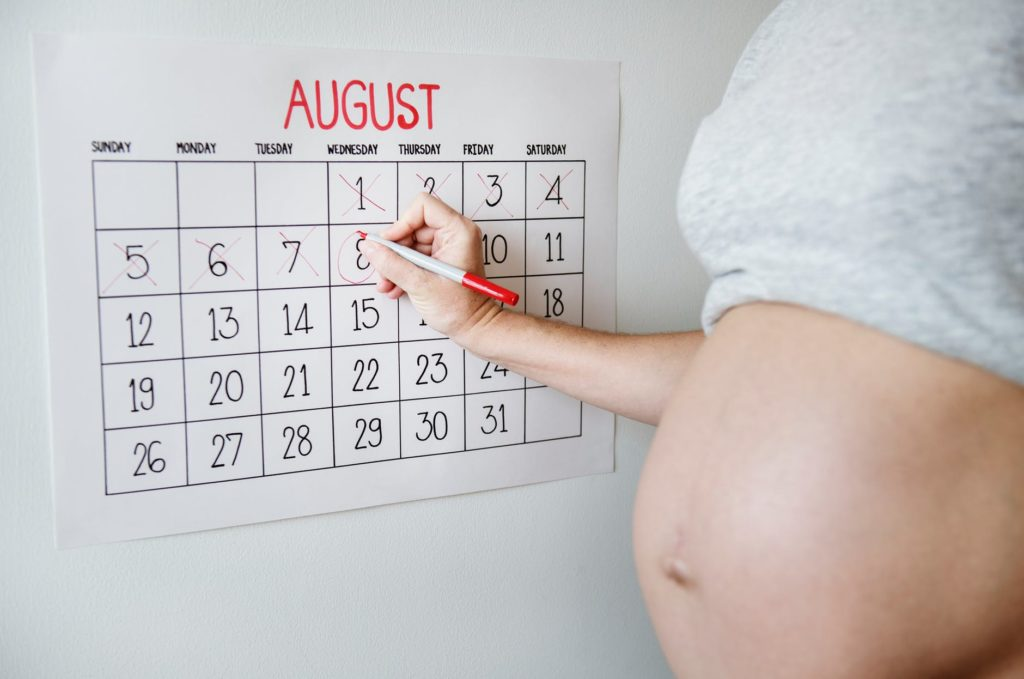 expectant lady holding pen marking calendar